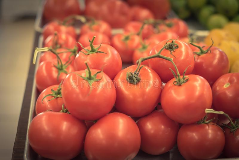 Cluster juicy tomatoes display at farmer market with price sign royalty free stock photo
