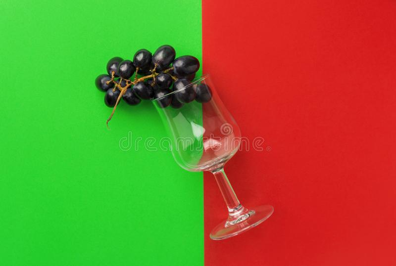 Cluster of moon drops dark purple grapes imitating wine in glass on duotone red green background. Wine production stock photos