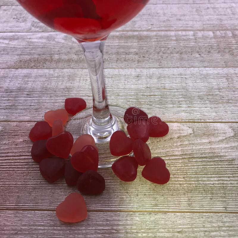 Glass of red wine with candy hearts at its base. On gray wooden background stock photography