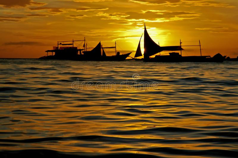 Cluster of sailboats silhouetted against a setting sun royalty free stock photos