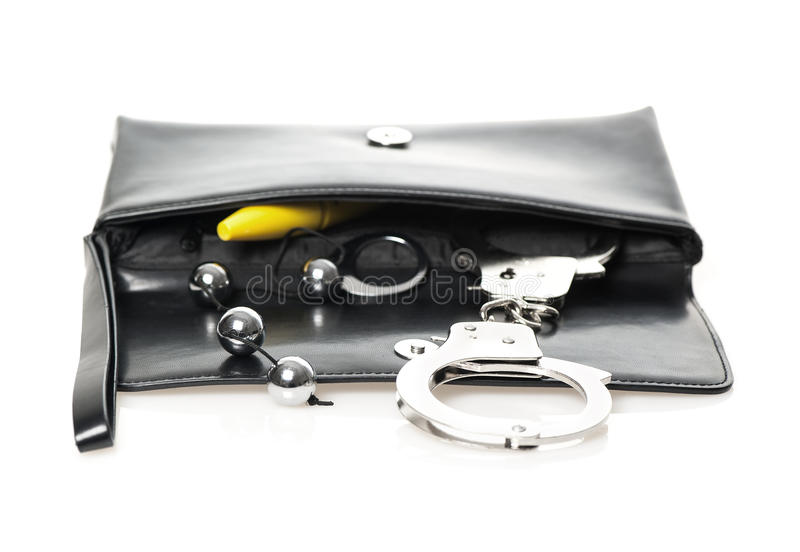 Clutch bag with explizit content. An open black clutch bag/purse with handcuffs, anal beads and a yellow dildo royalty free stock images