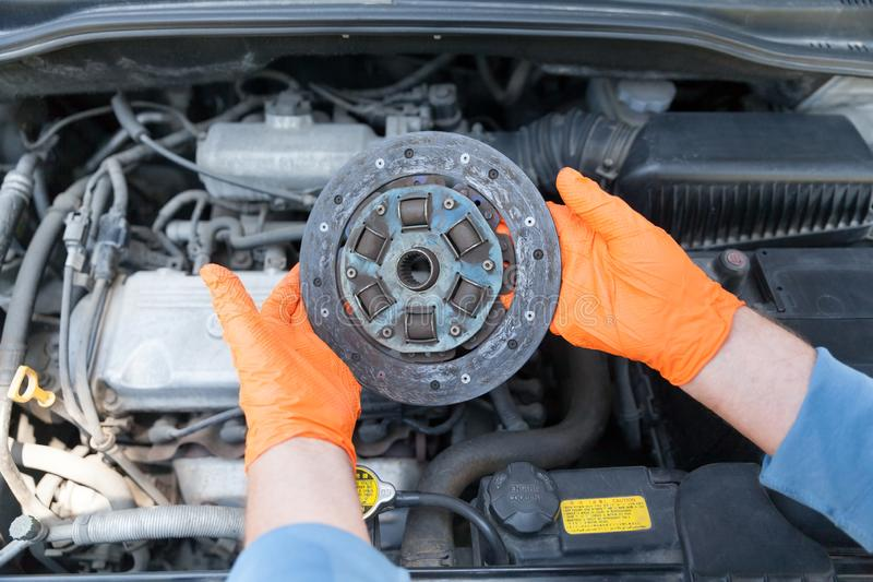 Auto mechanic wearing protective work gloves holds used clutch disc friction plate over a car engine. Old clutch disc friction plate stock image
