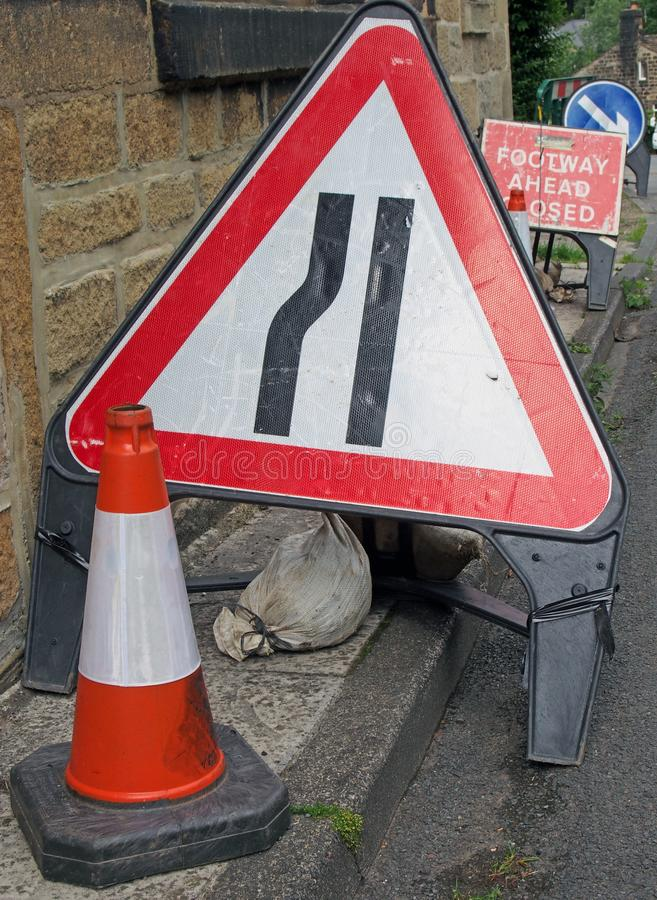 Clutter of temporary warning and direction signs at the side of a narrow country road while repair work is being carried out. A clutter of temporary warning and royalty free stock photography