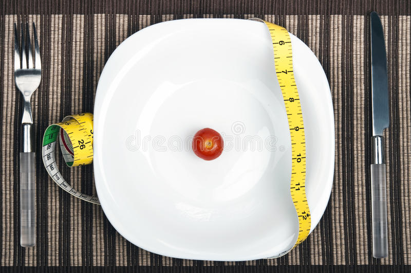 Cm ruler on food plate. Cm ruler and small tomato on plate royalty free stock photography