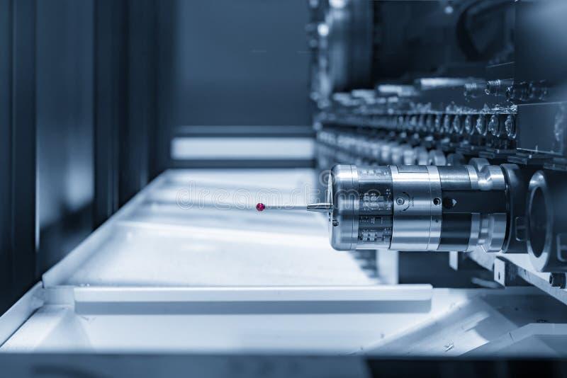 The CMM probe in the CNC machine magazine. In the light blue scene stock photo