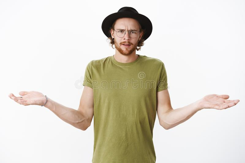 Cmon what wrong. Portrait of pissed, angry and confused bearded guy in glasses and hat frowning displeased and. Questioned, shrugging with hands spread sideways stock image