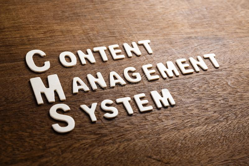 CMS Wood Letters. CMS Content Management System text by wood letters on wood texture stock photo