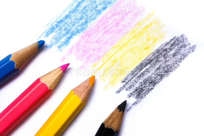 Cmyk concept - wooden crayon texture with cyan blue red magenta yellow and black drawings on white paper background. Cmyk concept / wooden crayon texture with stock photography
