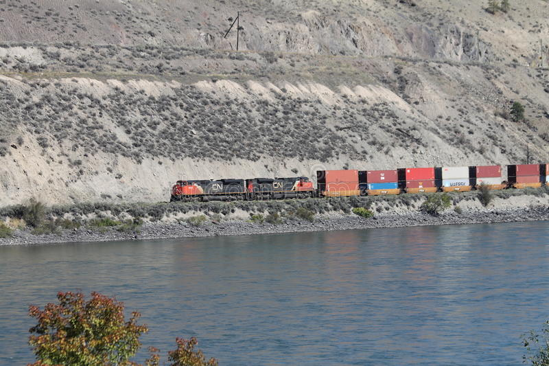 CN Freight Train near Spences Bridge BC. A Canadian National freight train pulling railcars loaded with shipping containers nears Spences Bridge in southern stock photography