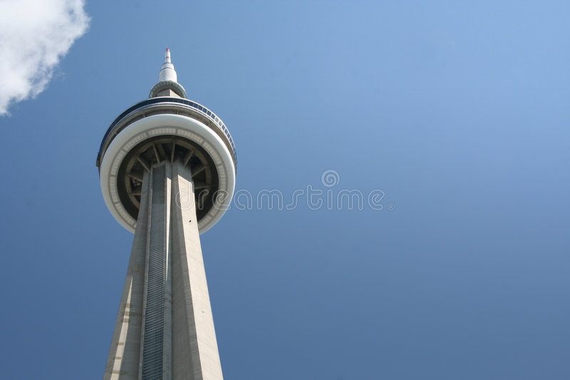 CN tower toronto. Ground view looking up at the CN tower with blue sky and clouds royalty free stock photography