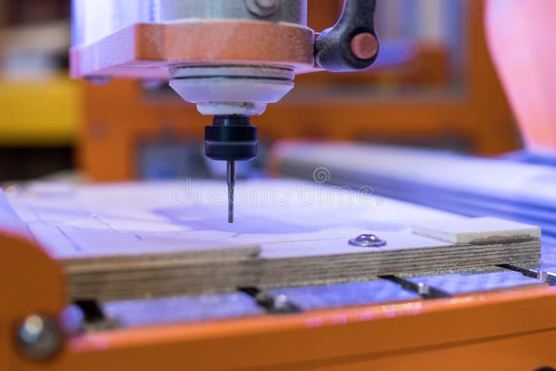 CNC μηχανή άλεσης χαράζοντας έναν ξύλινο πίνακα έλεγχος κοπτών στοκ εικόνες