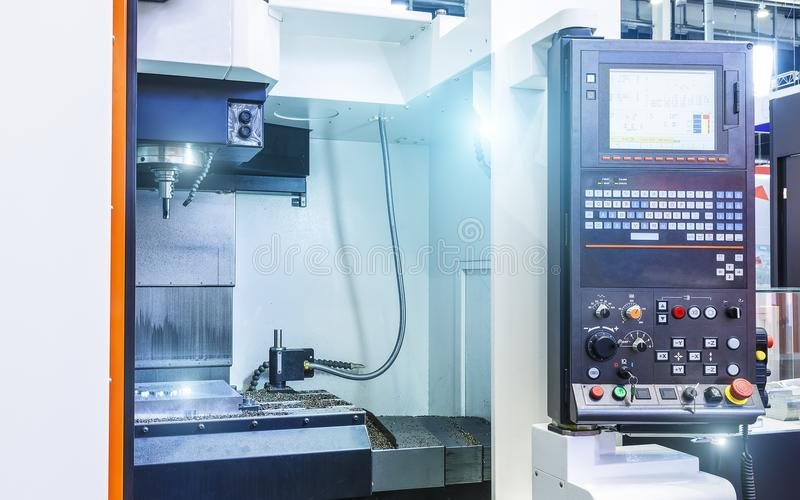 CNC control panel and open working area of the machine with vnturi lighting and metal chips, concept of modern royalty free stock photo