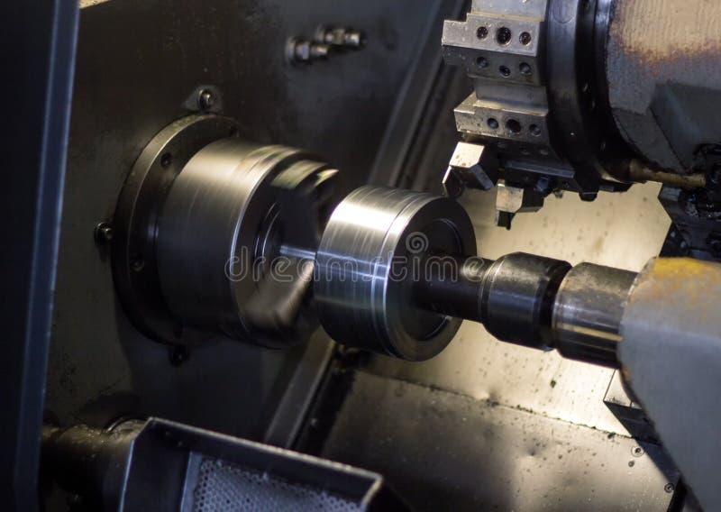 Cnc-Drehbank zieht Teil vom Metallwerkstückflaschenzug aus, moderne Drehbank für das verarbeitende Metall, Nahaufnahme, Maschine stockfotografie