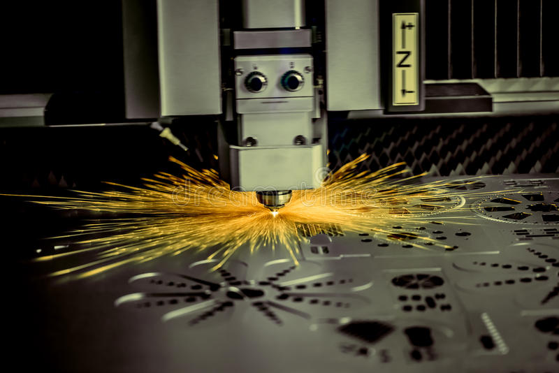 CNC Laser cutting of metal, modern industrial technology. . Small depth of field. Warning - authentic shooting in challenging conditions. A little bit grain stock photo