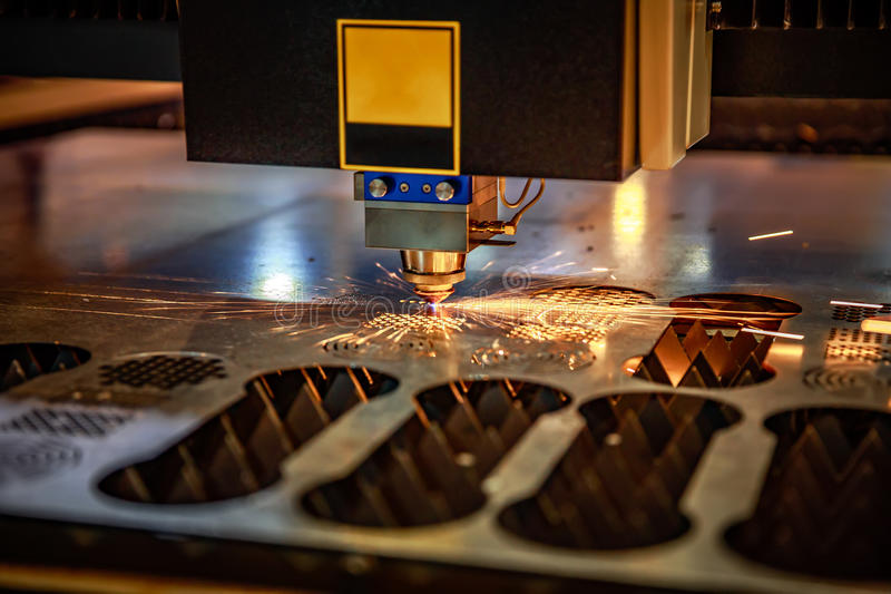 CNC Laser cutting of metal, modern industrial technology. . Small depth of field. Warning - authentic shooting in challenging conditions. A little bit grain stock photos
