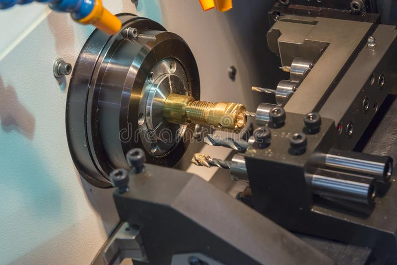 The CNC lathe machine cutting the brass shaft. With the drill tool stock image