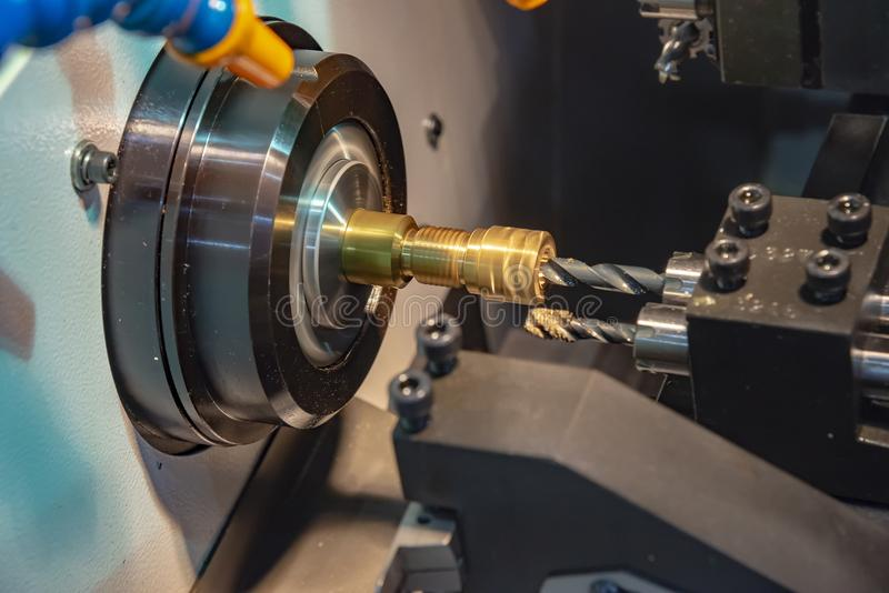 CNC lathe machine cutting the brass shaft. The CNC lathe machine cutting the brass shaft with the drill tool.The high technology manufacturing concept stock photo