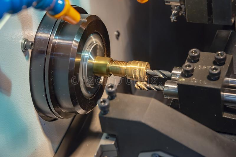 The CNC lathe machine cutting the brass shaft. With the drill tool.The high technology manufacturing concept stock photo