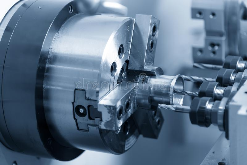 The CNC lathe machine making the hole on the metal part with drill tool. royalty free stock photography
