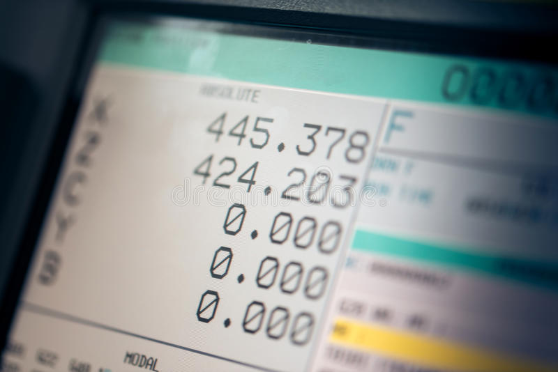 CNC machine monitor display with program code running and numbers stock image