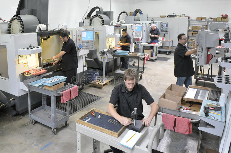 CNC Machine Shop. A modern sophisticated CNC machine shop with many workers royalty free stock images