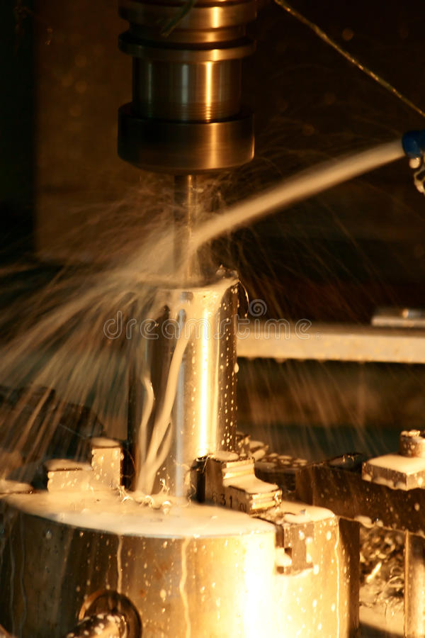 CNC Milling Machine. Is running in dilling process with lubricant cooling system royalty free stock photography
