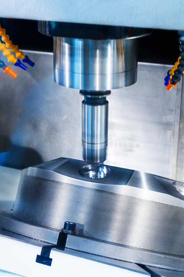 CNC milling machine during operation. Produce drill holes in the metal part stock photography