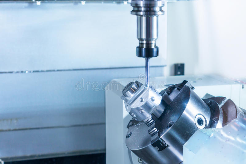 CNC milling machine during operation. Produce drill holes in the metal part stock photo