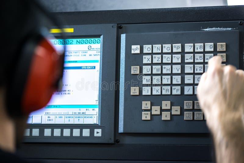 CNC operator przy metalu mielenia machining centrum w narzędziowych warsztatowych wkłada dane z klawiaturowy być ubranym, zdjęcie royalty free