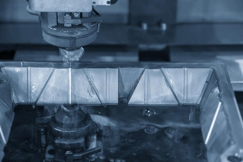 The CNC wire-edm machine cutting the metal plate stock image