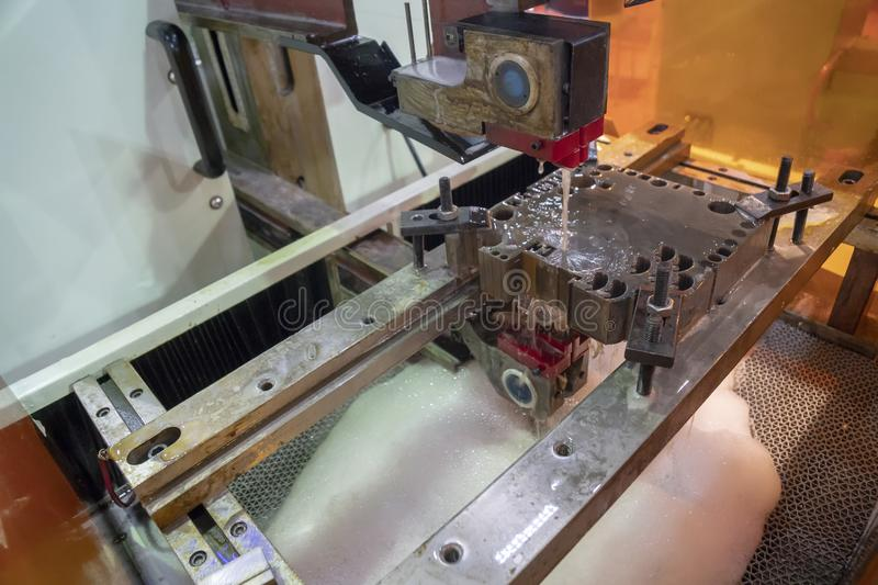 The CNC wire-EDM machine cutting the mold insert. stock photo