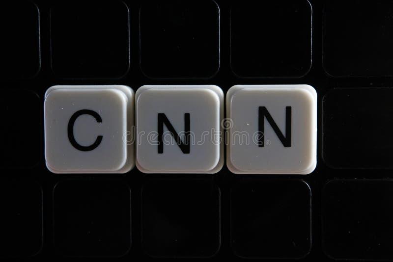Cnn控制文本词标题说明标签盖子背景背景 字母表信件在黑反射性背景的玩具块 免版税图库摄影