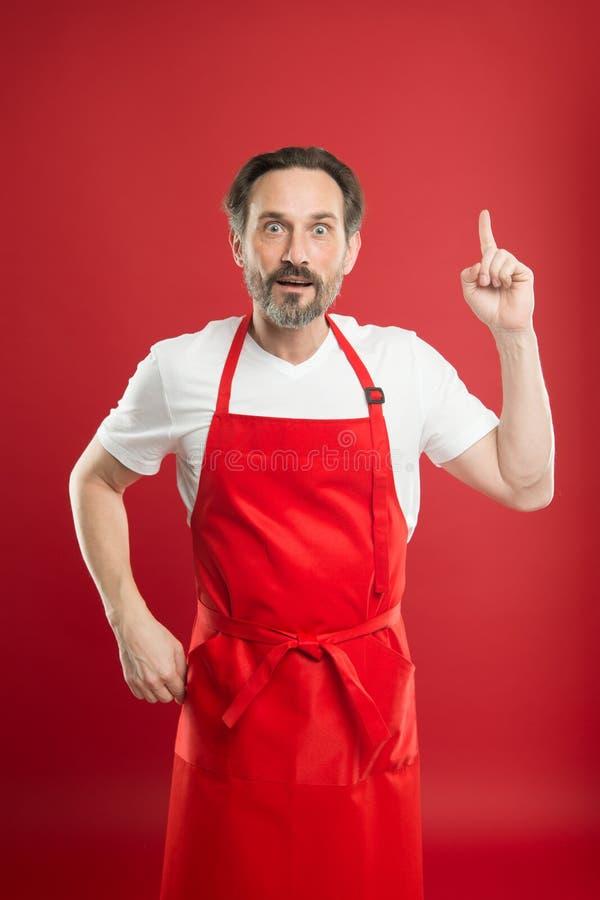 coś nowego Cook z brodą i wąsy jest ubranym fartuch czerwieni tło Mężczyzny dojrzały kucbarski pozuje kulinarny fartuch szef obraz stock