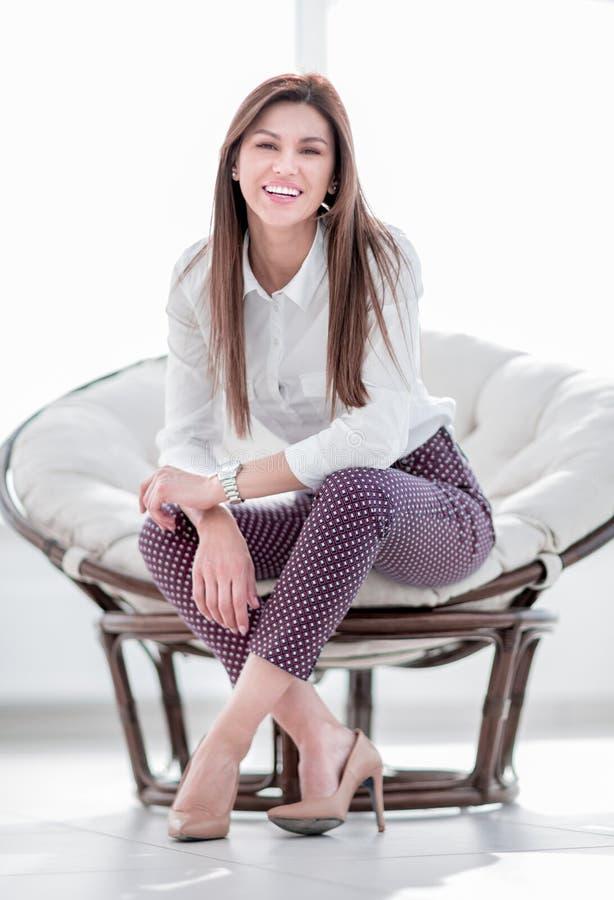 Современная молодая молодая женщина сидя в удобном стуле стоковая фотография
