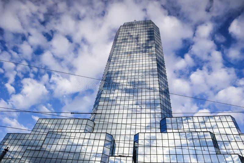 Современный отражательный небоскреб офиса против голубого неба с белыми облаками Варшава, Польша стоковое изображение