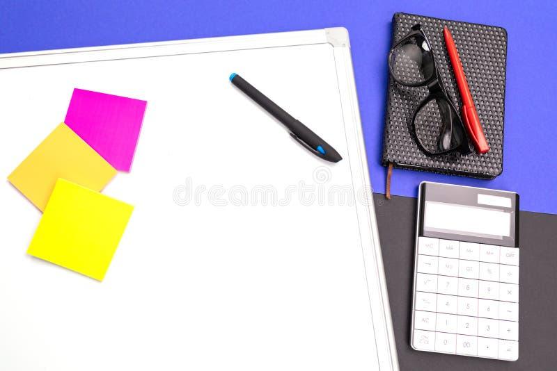 Современное рабочее место с офис-доской, ручкой и калькулятором изолированными на голубой черной предпосылке стоковое изображение rf