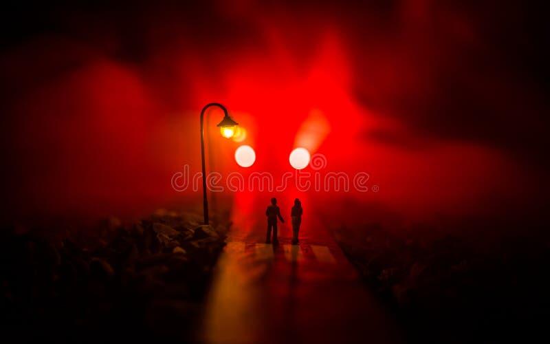 соедините каждо руки держа других детенышей Медленно идущ под белые уличные светы в ночи Темное время Мирная атмосфера в тумане стоковые фото