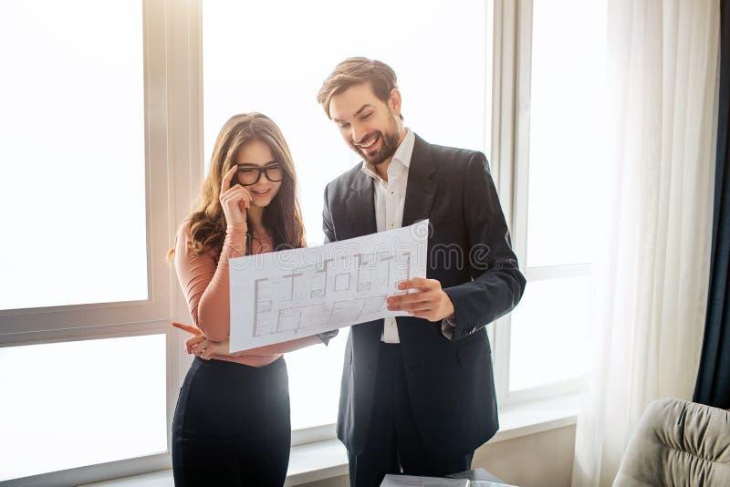 Соедините квартиру покупки или ренты совместно Молодая женщина в стеклах смотрит план и улыбку Жизнерадостный пункт человека на е стоковое фото rf