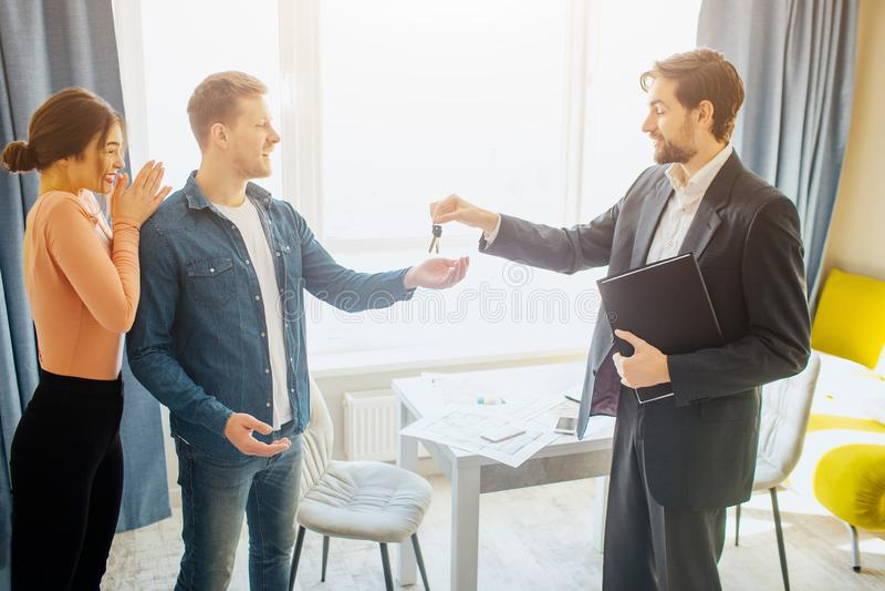 Соедините квартиру покупки или ренты совместно Риэлтор дает ключи молодому человеку Наслаждаться женщины счастливый жизнь новая К стоковые изображения