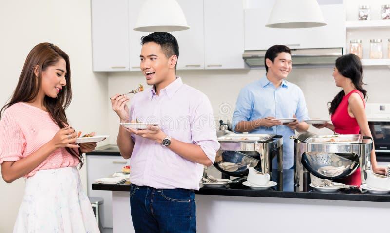 Соедините наслаждаться едой на приеме гостей стоковые фотографии rf