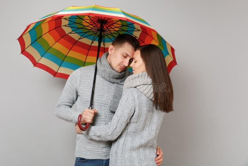 Соедините парня девушки в серых шарфах свитеров совместно под зонтиком изолированным на серой предпосылке стены, портрете студии стоковое фото