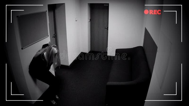 Сознавание в коридоре офиса, отравление женщины теряя, влияние камеры CCTV стоковое фото rf