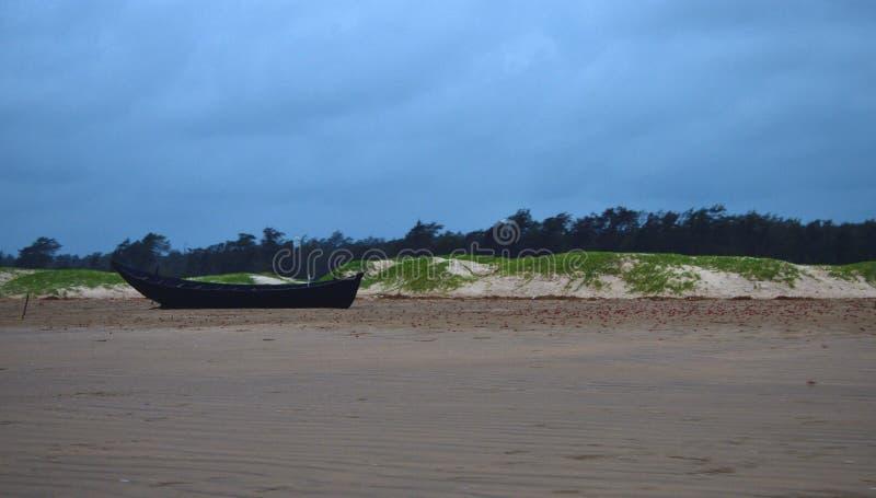 солитарный деревянный пляж рыбацкой лодки на море с пляжем и соснами песка стоковое изображение rf