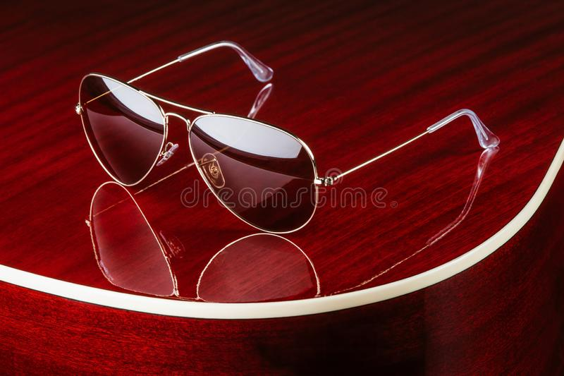 Солнечные очки стиля авиатора на лоснистой гитаре стоковая фотография