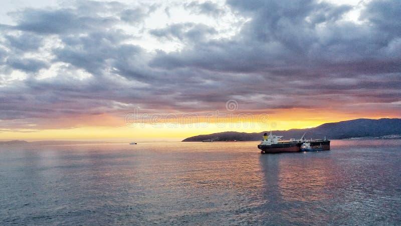 Солнце устанавливает над Гибралтарскими Залив по мере того как топливозаправщики ждут в заливе стоковые изображения rf