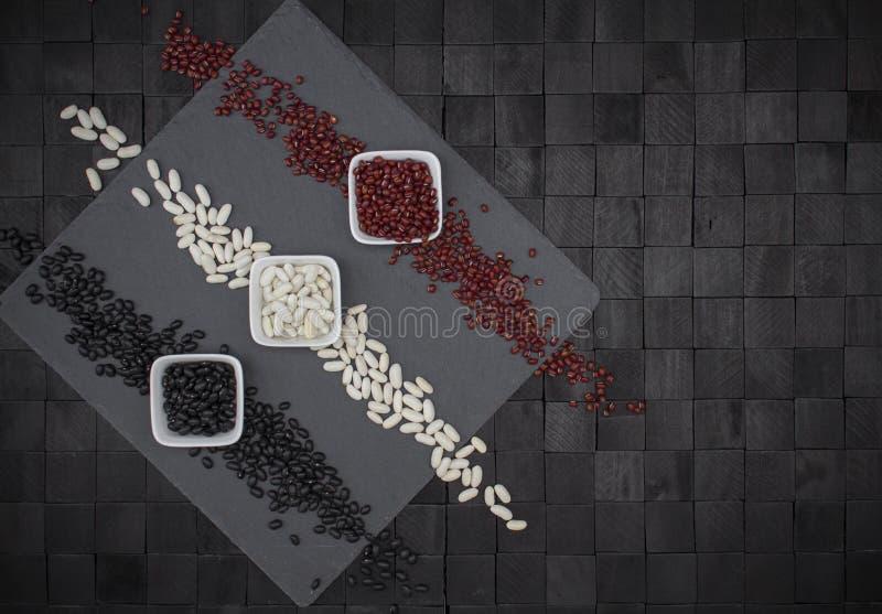 Состав дизайна предпосылки сверху с квадратной плитой шифера и 3 шарами с фасолями других цветов которые составляют 3 стоковые фото