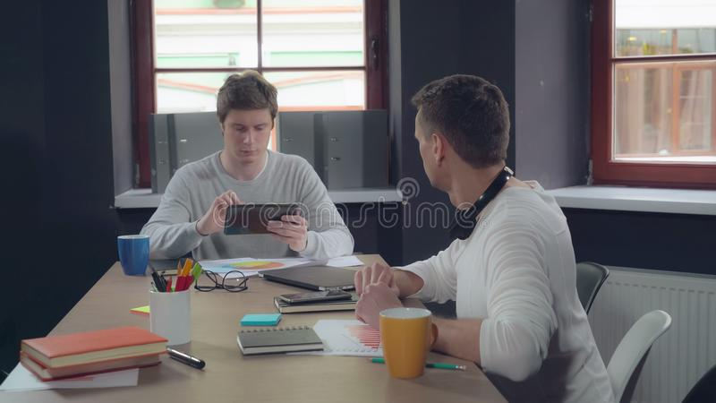 Сотрудники на дискуссии места службы о отчете стоковое изображение