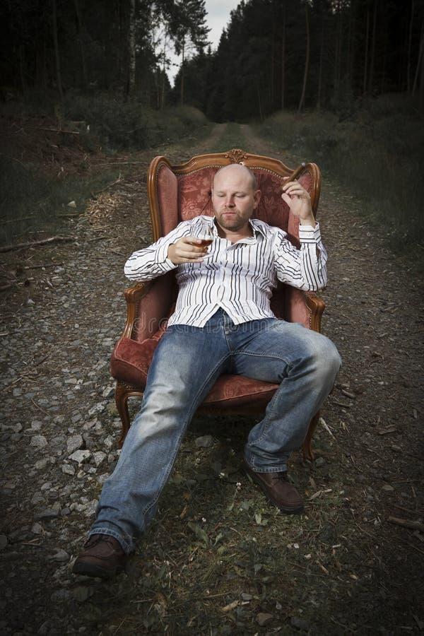 Coñac de consumición del hombre pensativo en una silla del vintage imagen de archivo libre de regalías