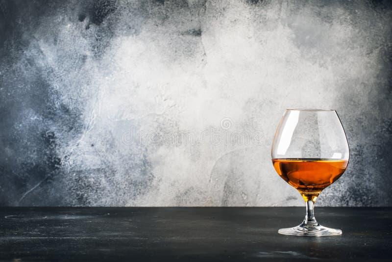 Coñac o brandy en la copa de vino, fondo gris del contador de la barra de la piedra, foco selectivo imágenes de archivo libres de regalías