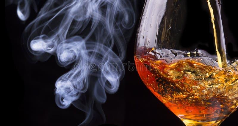 Coñac o brandy en un negro con humo del cigarro imagenes de archivo